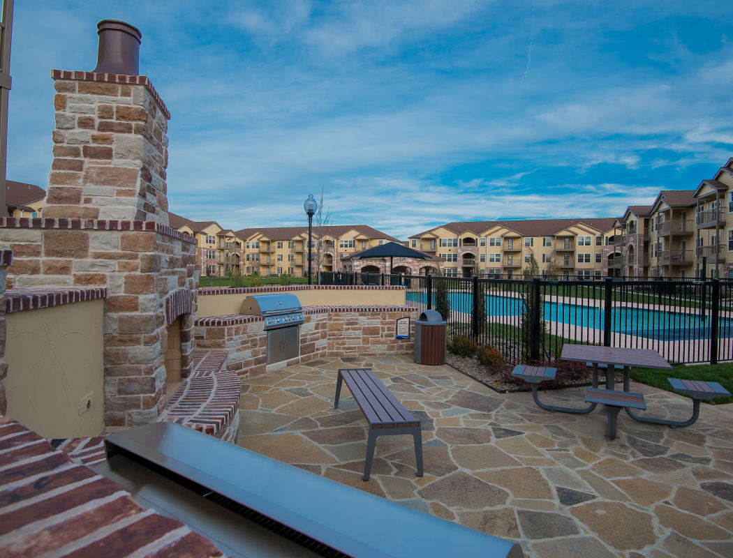 Outdoor patio by the pool at Portico at Friars Creek Apartments in Temple, Texas