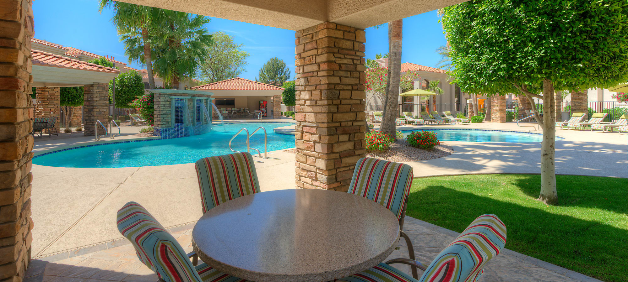 Outdoor seating next to the swimming pool at San Prado in Glendale, Arizona