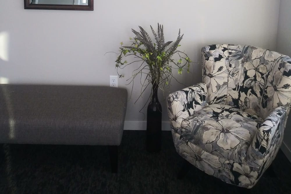 Resident sitting area with cozy chair and bench at Arlington Place of Red Oak in Red Oak, Iowa