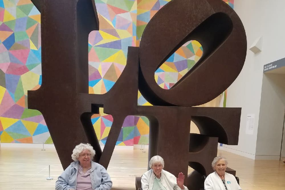 Three residents in front of large letters spelling love at The Springs of Mooresville in Mooresville, Indiana