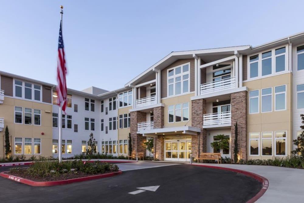 Exterior of main building with a flag at Merrill Gardens at Huntington Beach in Huntington Beach, California.