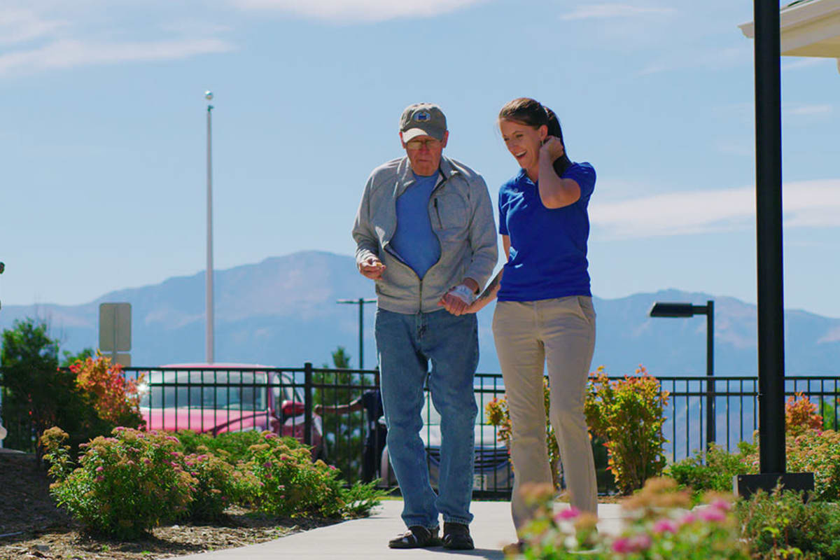 Staff and resident walking outside at New Dawn Memory Care in Colorado Springs, Colorado