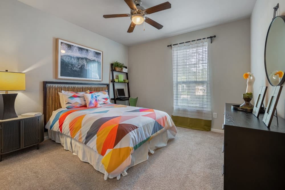 Carpeted bedroom with window and ceiling fan at Marquis at Sugar Land in Sugar Land, Texas