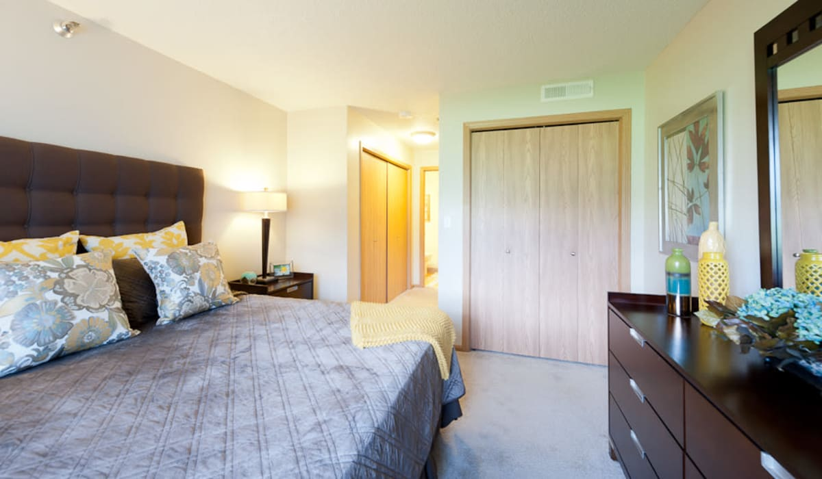 The main bedroom with plush carpeting and a ceiling fan at Pointe West Apartment Homes in West Des Moines, Iowa