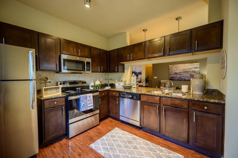 Dark wood cabinetry in model kitchen at Pecan Springs Apartments in San Antonio, Texas