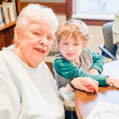 A young boy and a resident smile for the camera at Arbor Glen Senior Living in Lake Elmo, Minnesota