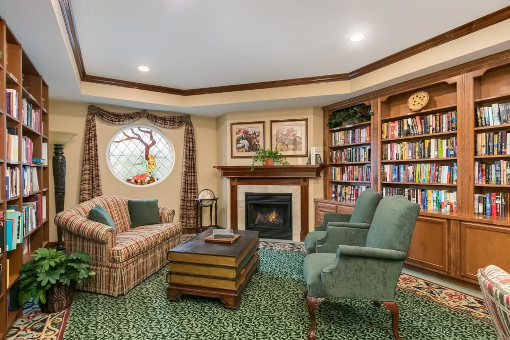 Library with books and fireplace at Applewood Pointe Woodbury in Woodbury, Minnesota.