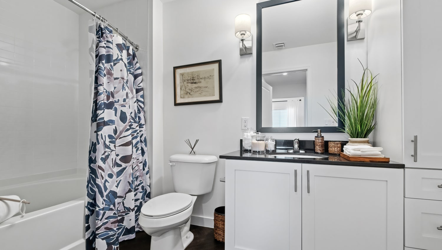 Model bathroom with white European style cabinets and tub/shower combination at Town Lantana in Lantana, Florida