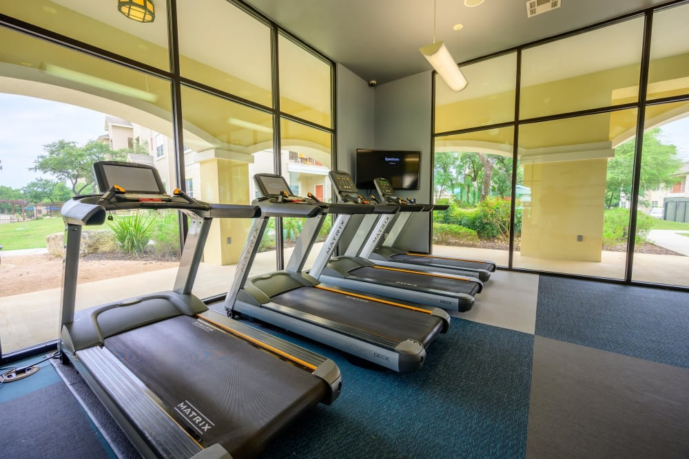 Fitness area with floor to ceiling windows for a great view while running at Pecan Springs Apartments in San Antonio, Texas