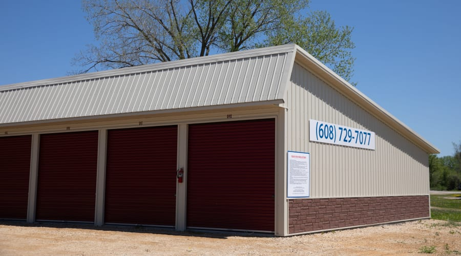 Storage units with brown doors and trees in the background at KO Storage of Tomah - Washington in Tomah, Wisconsin