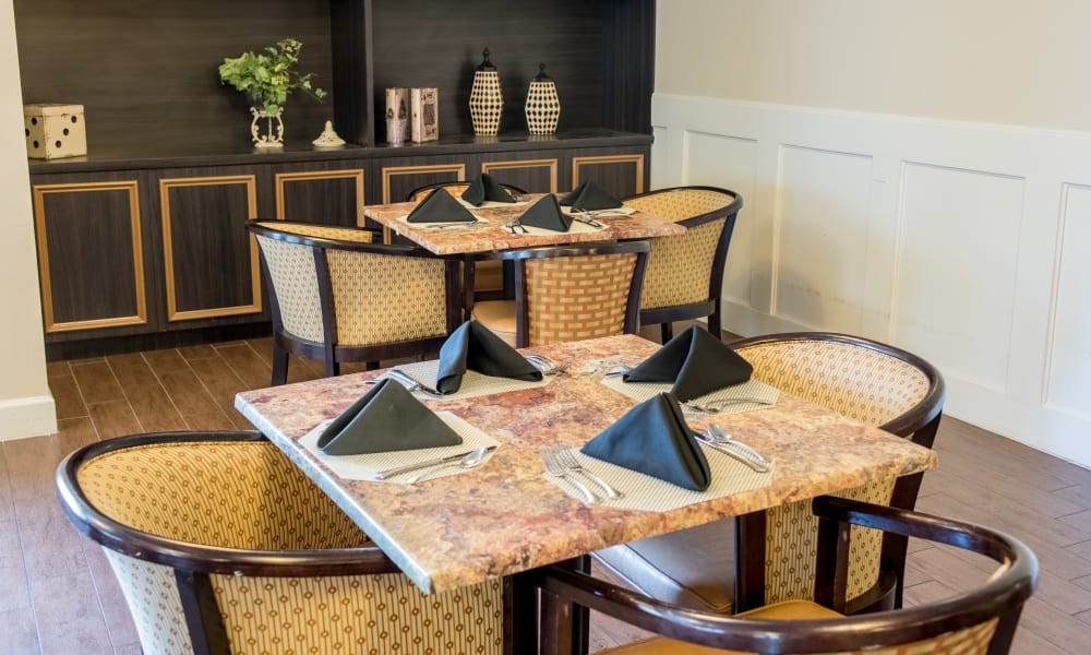 Resident dining room with black napkins at Inspired Living at Sun City Center in Sun City Center, Florida