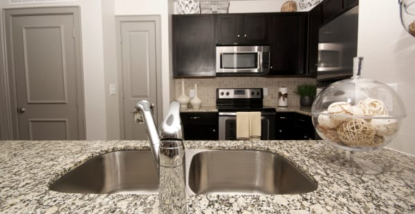 Spacious kitchen with tall chairs in model apartment home at The Sovereign in Fort Worth, Texas