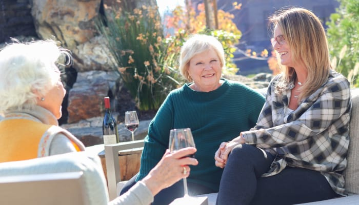 Resident enjoying a glass of wine outside at a The Springs Living community