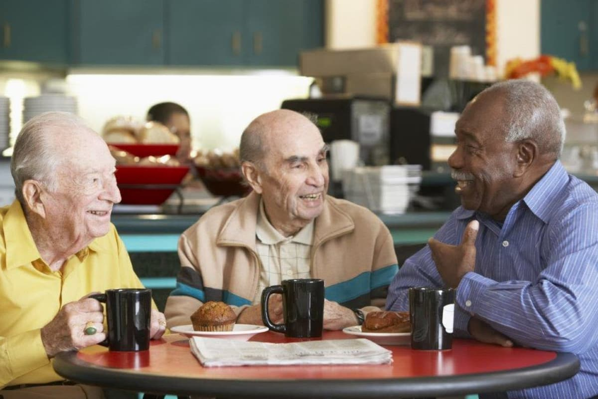 Three residents catching up over coffee at Avenir Memory Care at Scottsdale in Scottsdale, Arizona.
