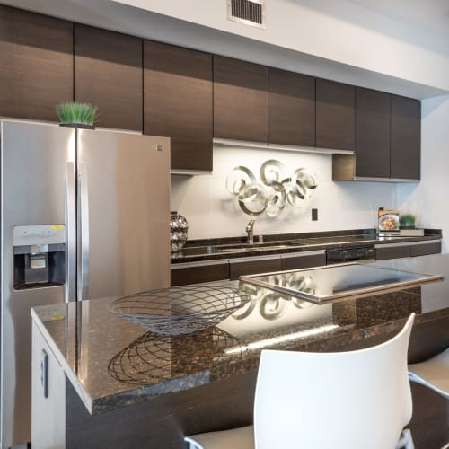 Gourmet kitchen with an island and granite countertops in a model home at Mosaic Dallas in Dallas, Texas