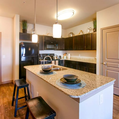 Gourmet kitchen with an island and granite countertops in a model home at Anatole on Briarwood in Midland, Texas