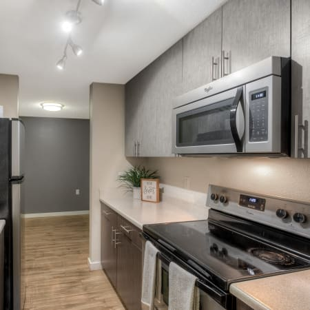 kitchen with light cabinetry and stainless steel appliances at Karbon Apartments in Newcastle