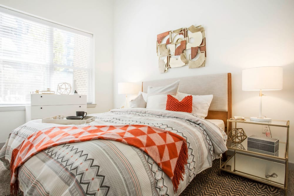 Bright and comfy bedroom with full size bed, dresser, and side tables at Marq Midtown 205 in Charlotte, North Carolina