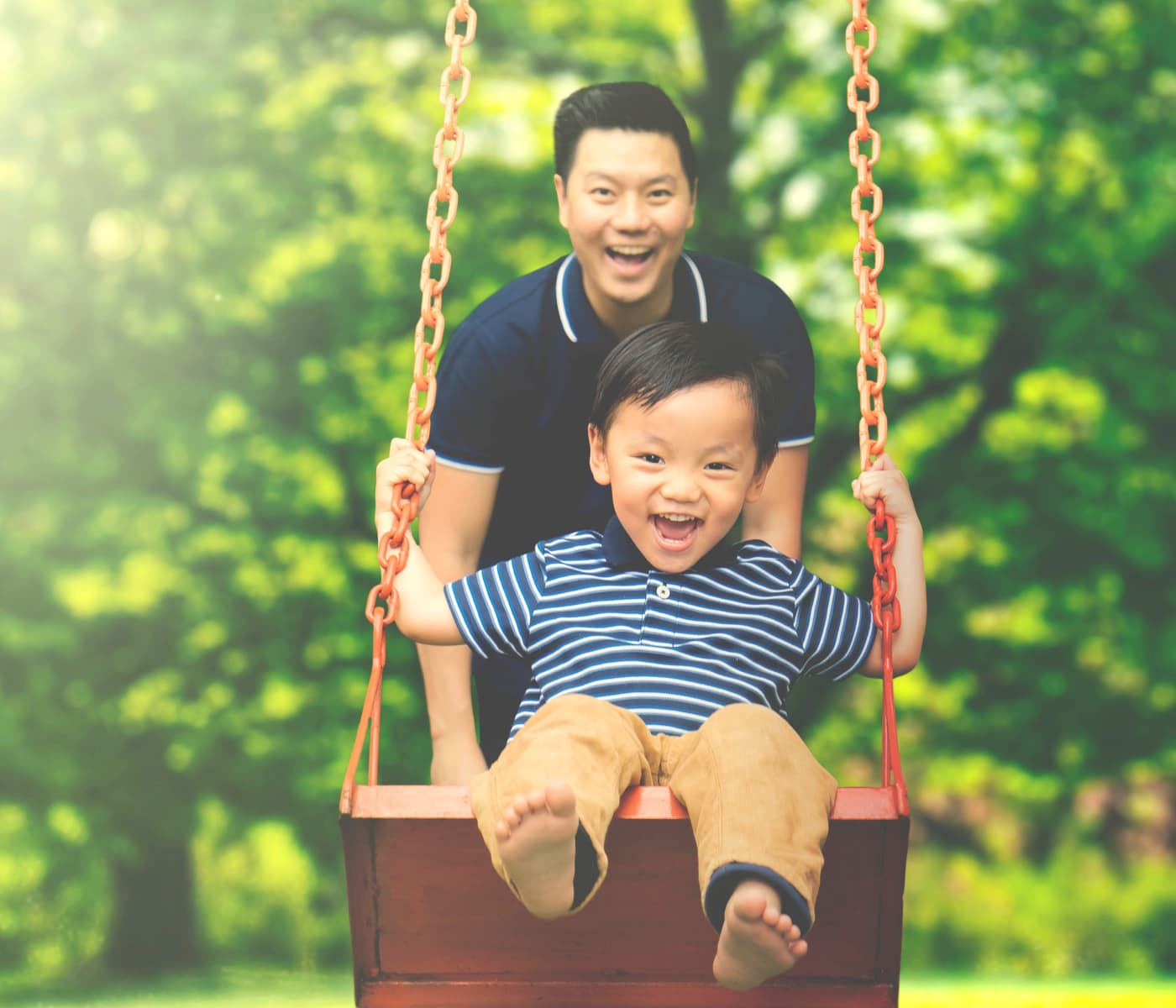 Father pushing his son on the swing in Derwood, Maryland near Shady Grove Apartments