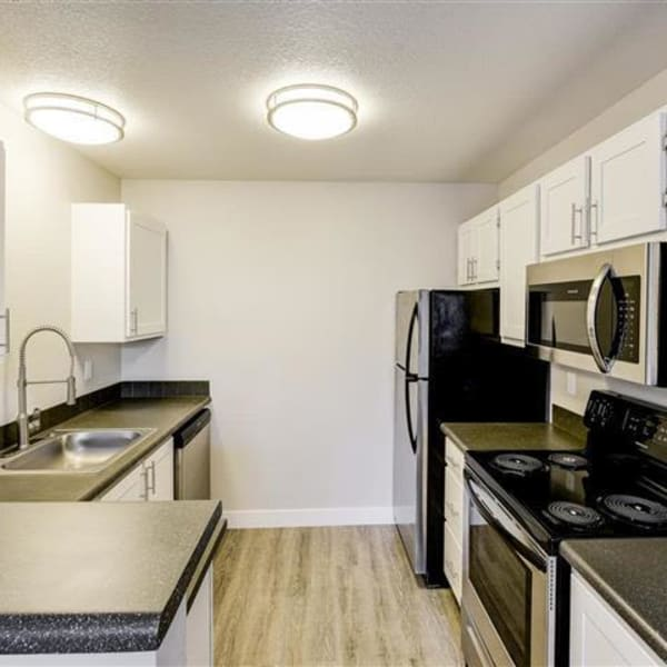 Kitchen with black appliances and stainless-steel sink at Northwind Apartments in Reno, Nevada