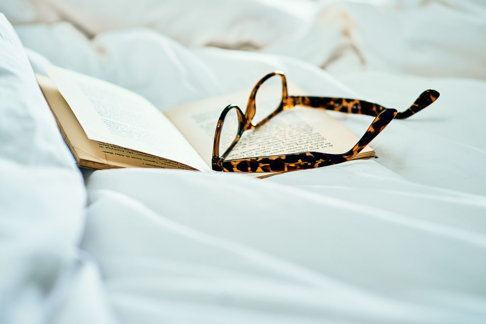 A book and some reading glasses sitting on a bedcover at The Meridian at Brandon in Tampa, Florida