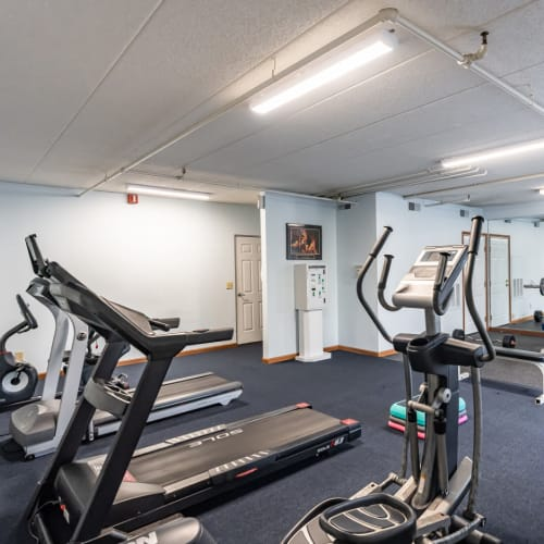 A fitness center with individual workout stations at Vantage Pointe West Apartments in Cincinnati, Ohio