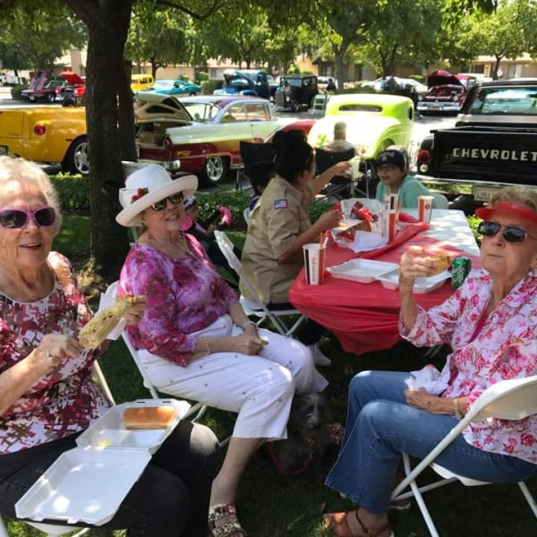 Residents eating outside at a community event at Quail Park on Cypress in Visalia, California