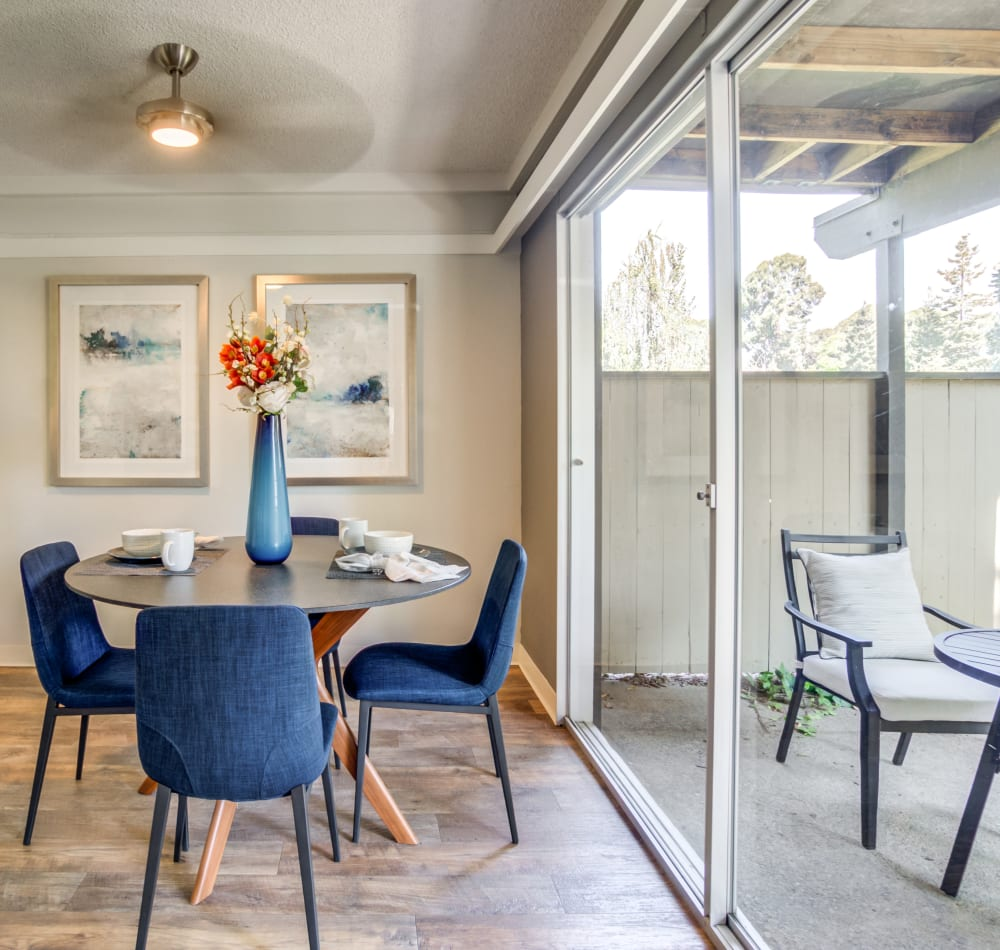 Dining area with a ceiling fan next to a model home's private patio at Sofi Fremont in Fremont, California