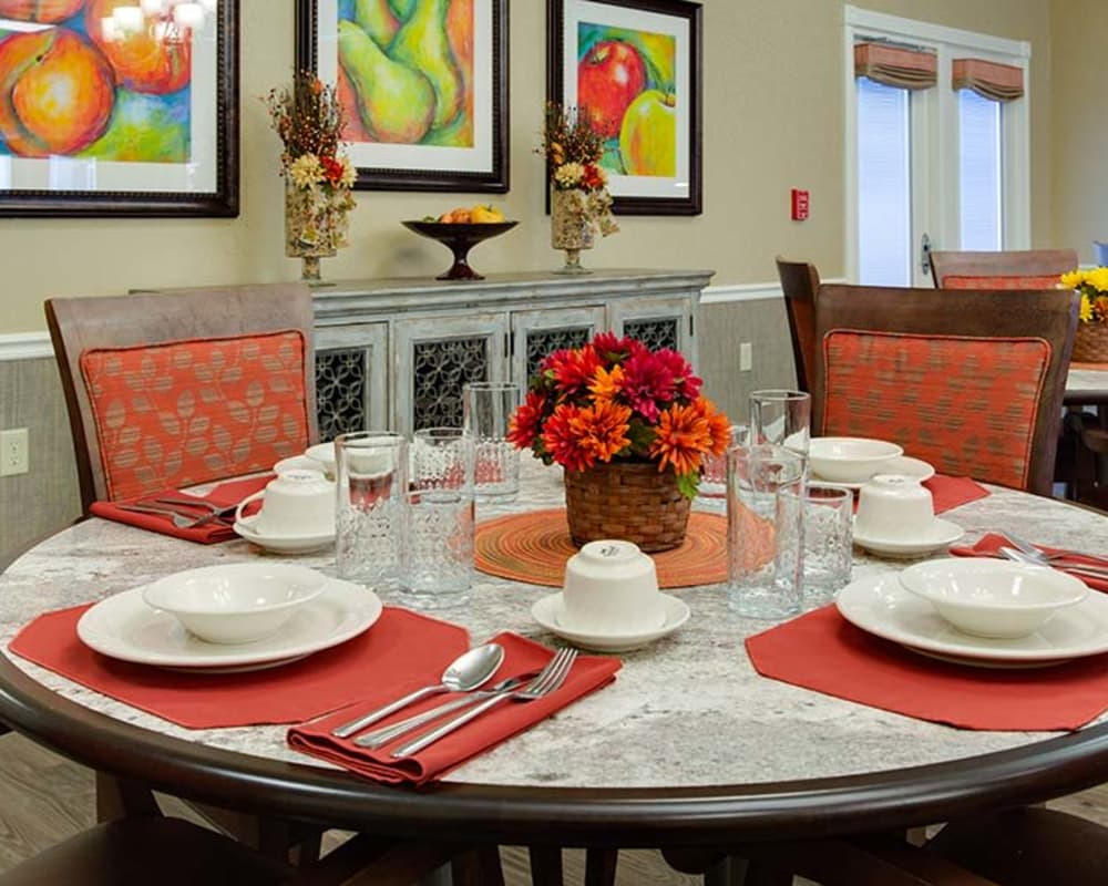 Well decorated dining area table with a view of the kitchen at Willow Springs Senior Living in Spring Hill, Tennessee
