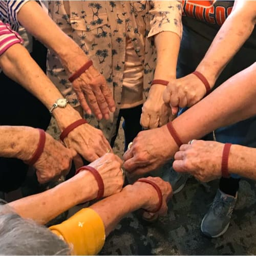 Residents holding their hands in a circle at Oxford Villa Active Senior Apartments in Wichita, Kansas