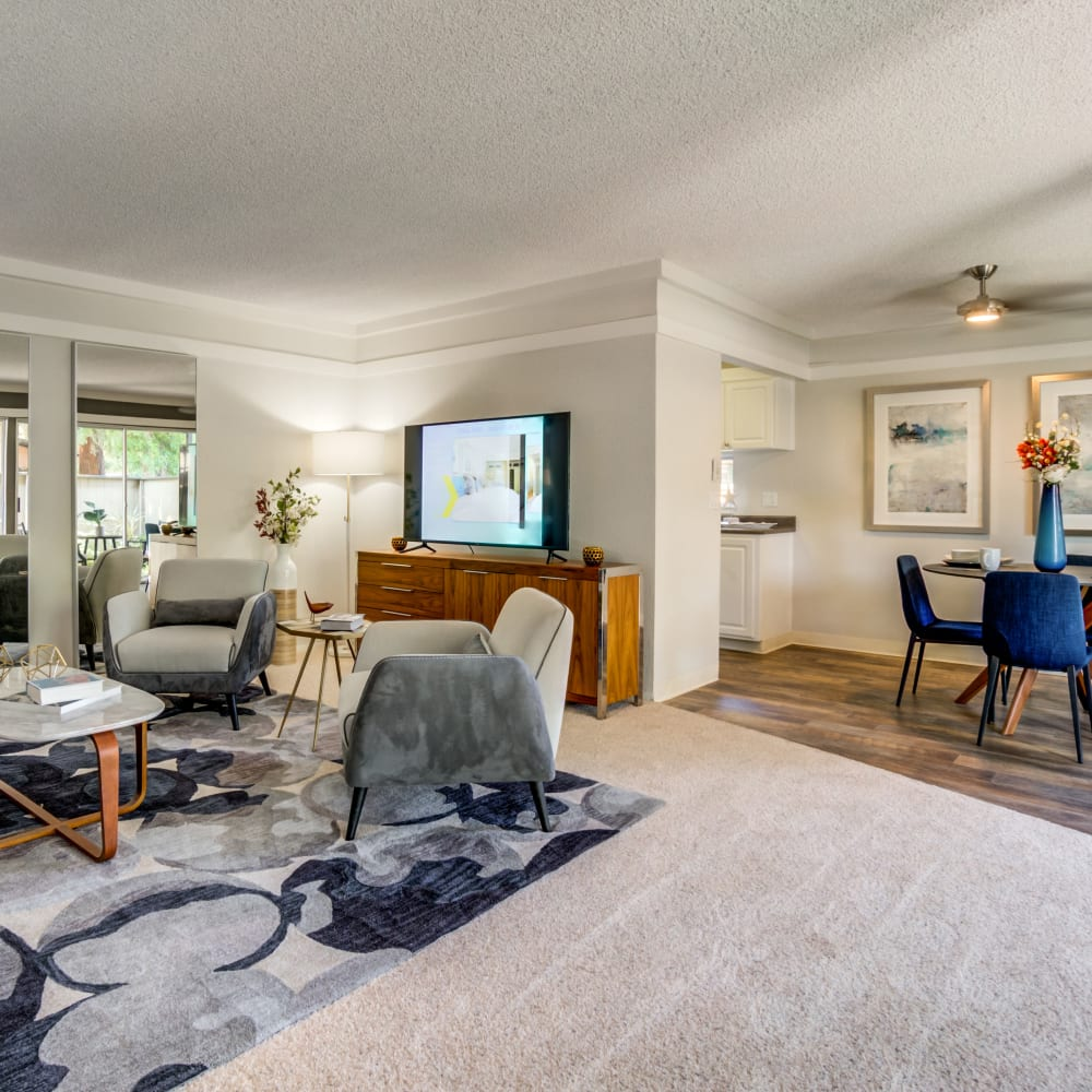 Open-concept living and dining areas with a ceiling fan and plush carpeting in a model home at Sofi Fremont in Fremont, California