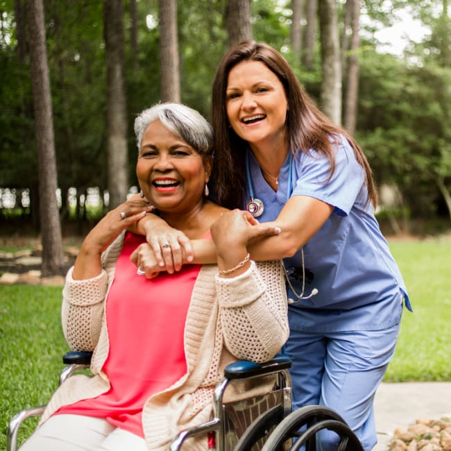 A resident and a CNA outside at an Americare community
