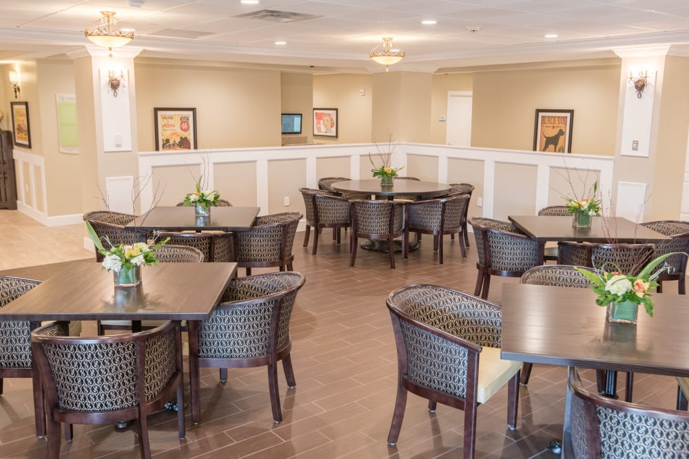 Dining area with flower centerpieces at Inspired Living Bonita Springs in Bonita Springs, Florida.