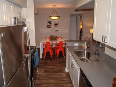 An apartment kitchen and dining table at Onyx Winter Park in Casselberry, FL
