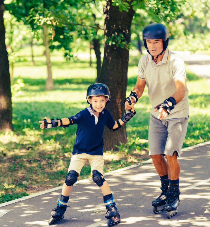 Father and son rollerblading near Camelot Court in Brighton, Massachusetts