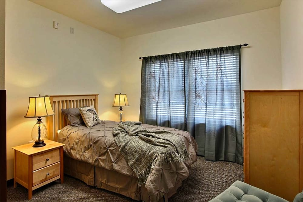 Cozy resident bedroom with side table and dresser at Milestone Senior Living in Woodruff, Wisconsin.