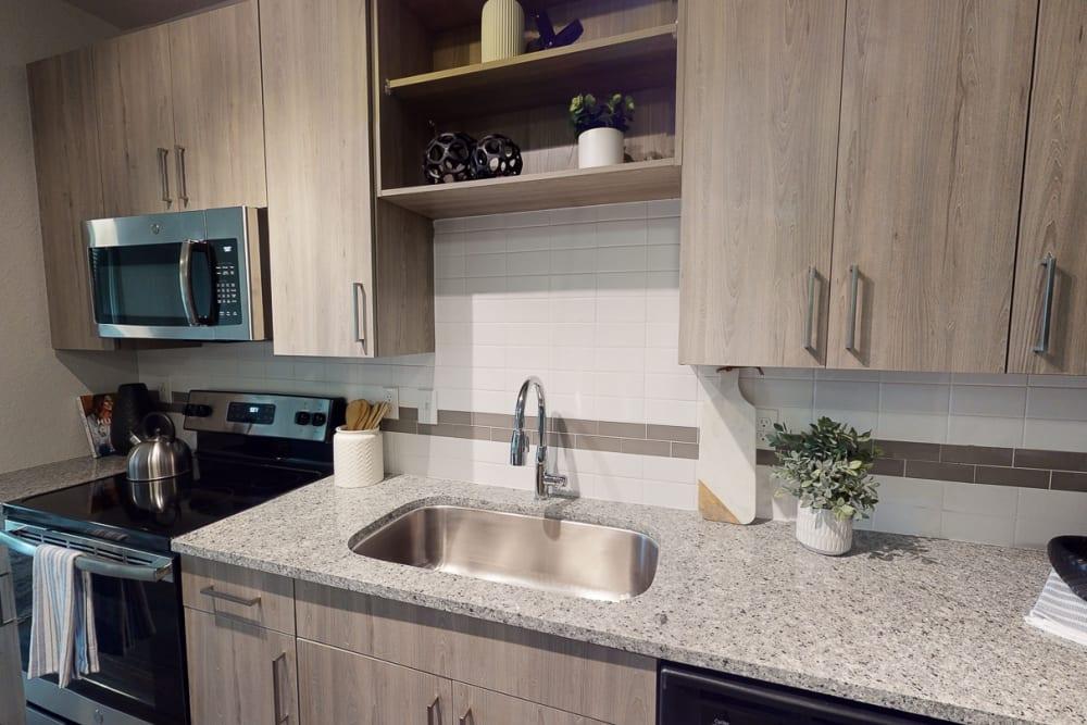 Model kitchen with granite countertops at Integra 289 Exchange in DeBary, Florida
