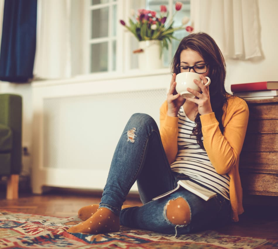 Resident relaxing with a cup of tea on the floor of the living area of her new home at Terra Martinez in Martinez, California