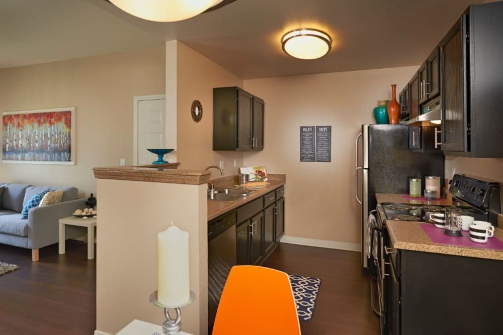 Kitchen with wood-style flooring at Crossroads at City Center Apartments in Aurora, Colorado