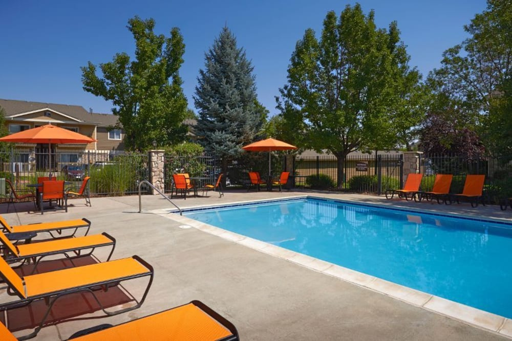 Beautiful resort-style swimming pool with lounge chairs at Crossroads at City Center Apartments in Aurora, Colorado