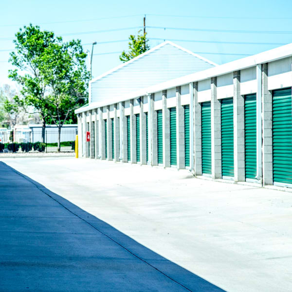 Outdoor storage units with green doors at StorQuest Self Storage in Aurora, Colorado