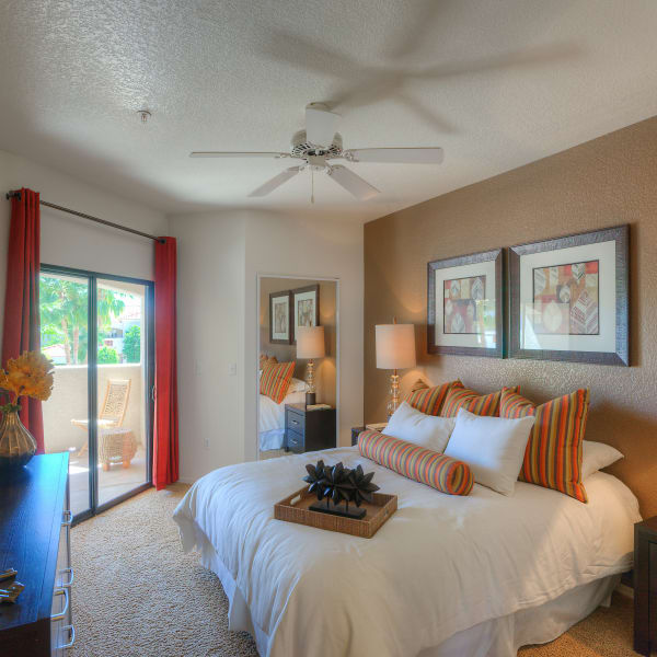 Well-decorated master bedroom with ceiling fan and sliding door to private balcony of model home at San Prado in Glendale, Arizona