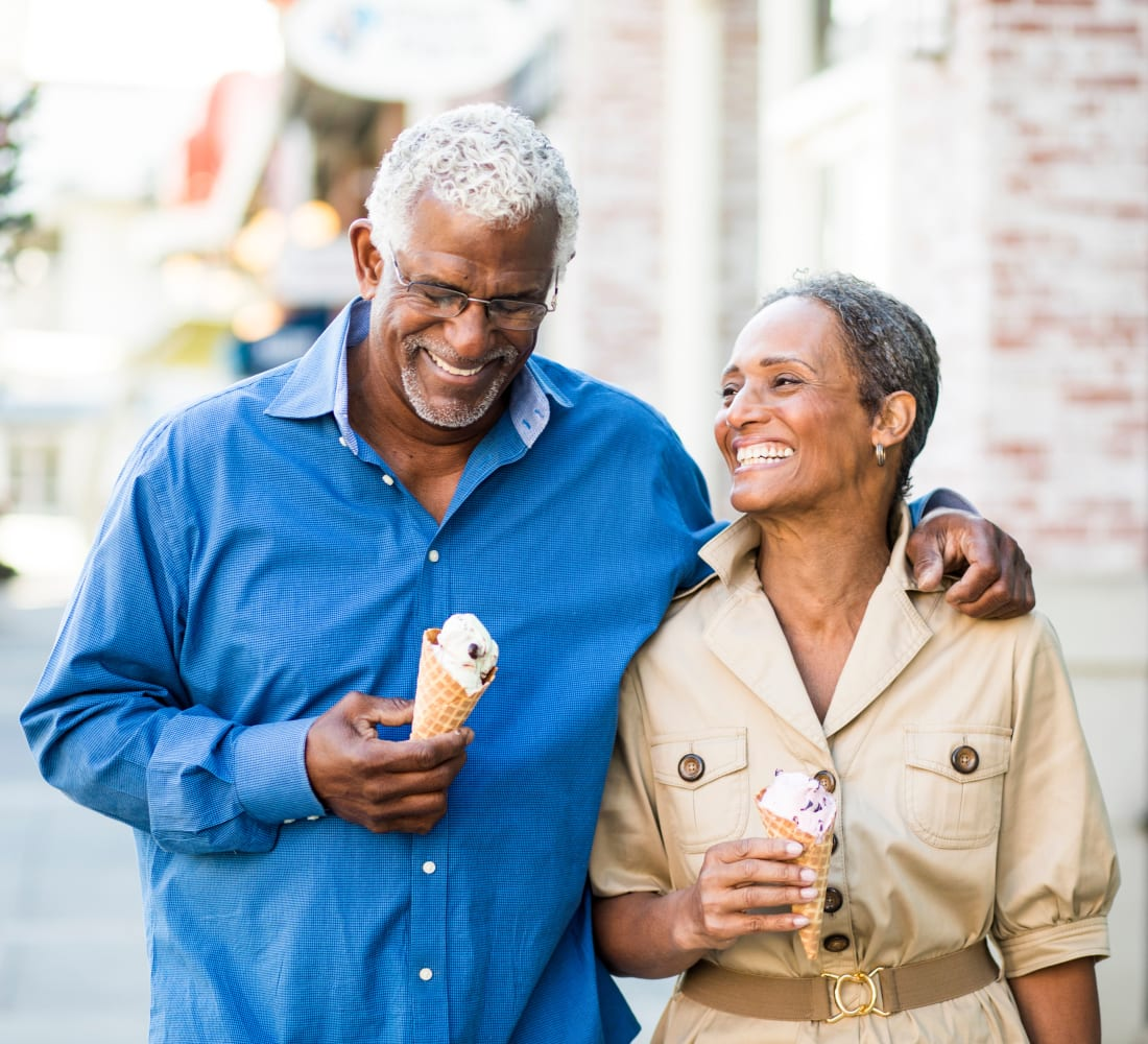 Resident couple walking around town eating ice cream cones near Pioneer Village in Jacksonville, Oregon