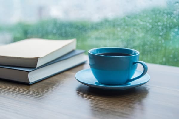 A cup of coffee and books on a table near a window at Farmington Square Medford in Medford, Oregon