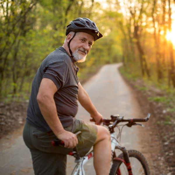 A man biking on a trail near  The Atrium at Carmichael in Carmichael, California