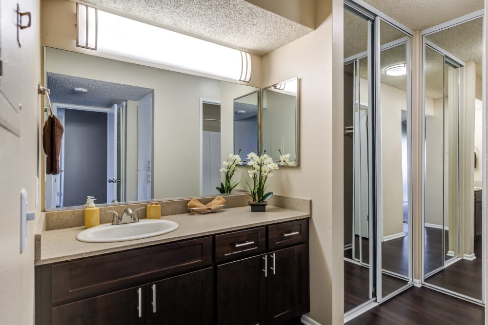 A renovated bathroom with a large vanity and a mirrored closet door at Kendallwood Apartments in Whittier, California