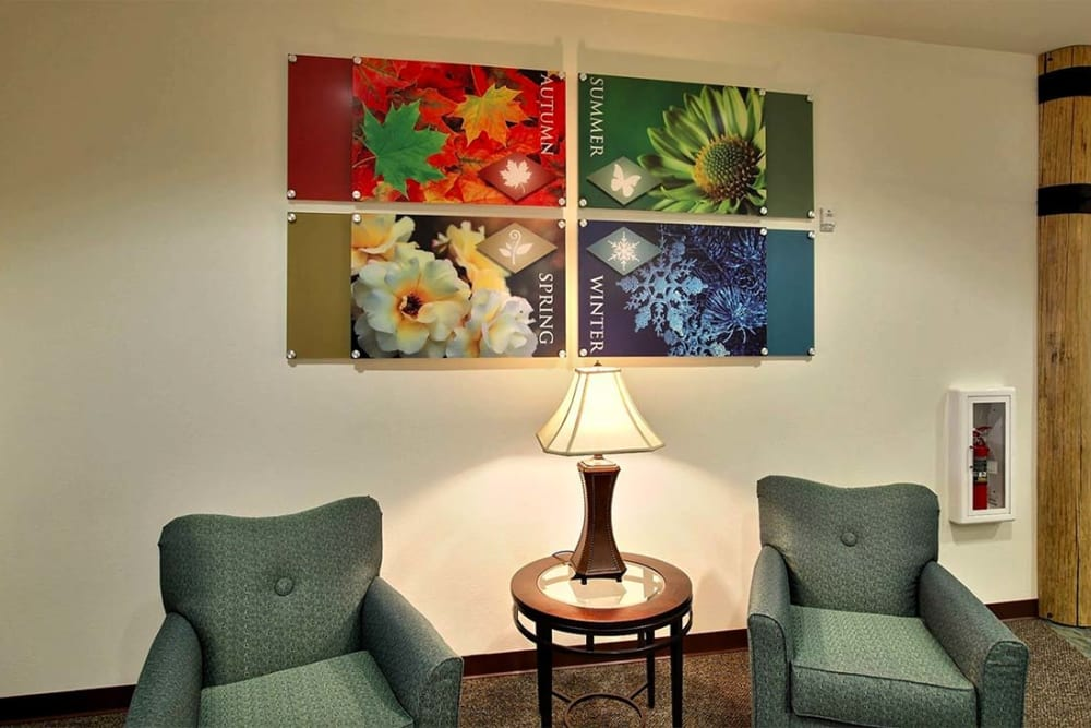 Cozy seating nook with artwork at Milestone Senior Living in Woodruff, Wisconsin.