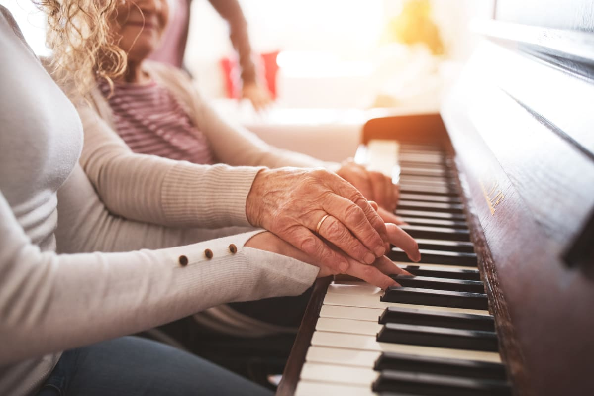 A resident playing the piano at The Oxford Grand Assisted Living & Memory Care in Kansas City, Missouri