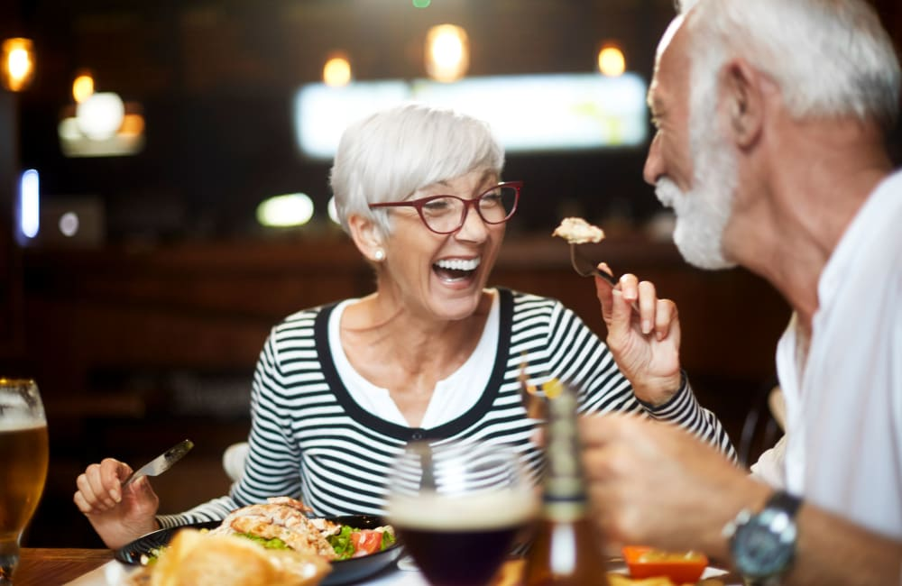 Couple chatting over dinner at Campus Commons Senior Living in Sacramento, California