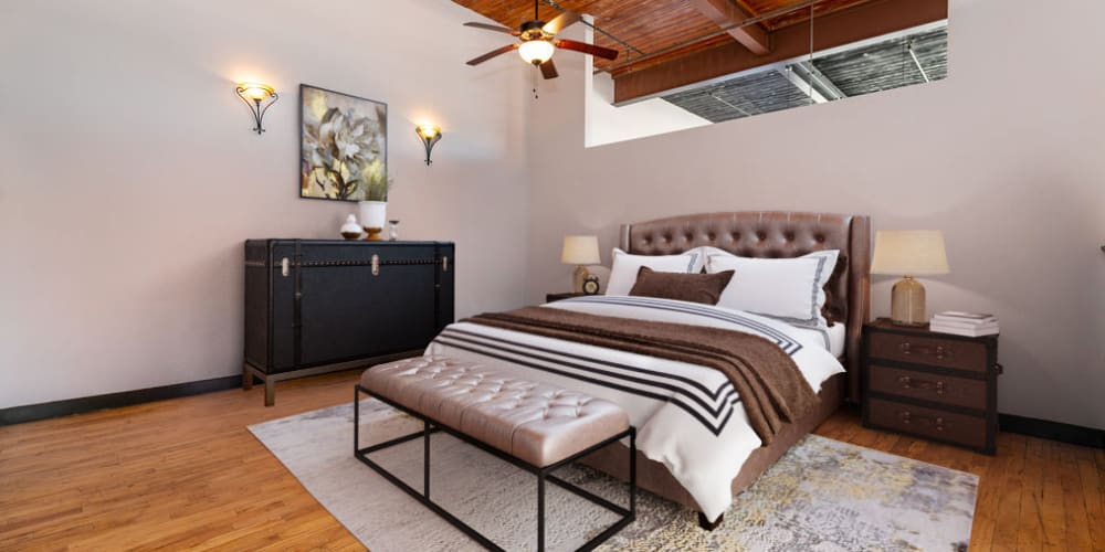 Cozy bedroom with a ceiling fan at The Lofts at Swift Mill in Columbus, Georgia